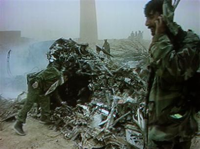 In this image taken from video, Afghan security forces inspect the wreckage of a U.S. military CH-47D Chinook helicopter.